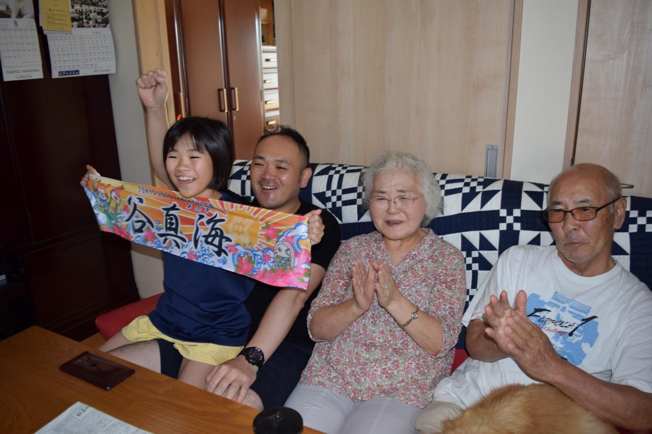 テレビの前で応援する同級生の畠山さんら家族