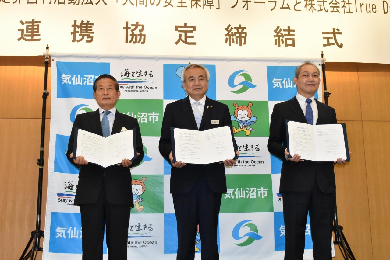 協定書を交わした高須理事長(左)菅原市長(中)米倉社長