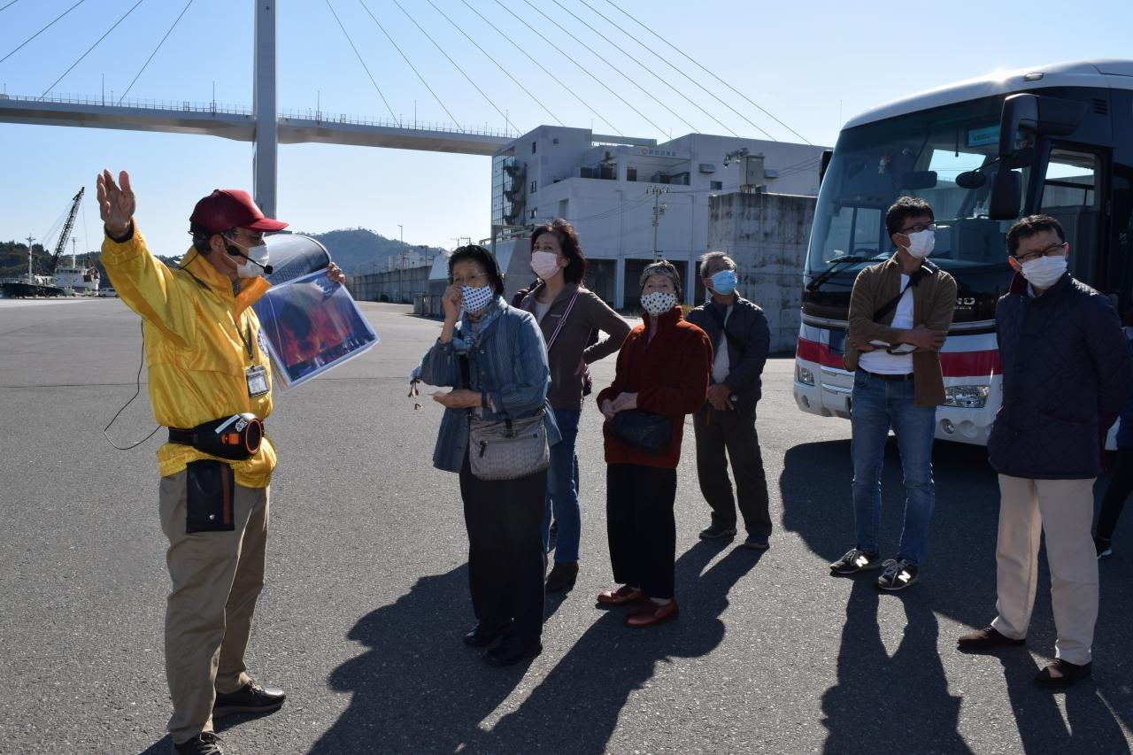 語り部の話に耳を傾ける観光客(商港岸壁)