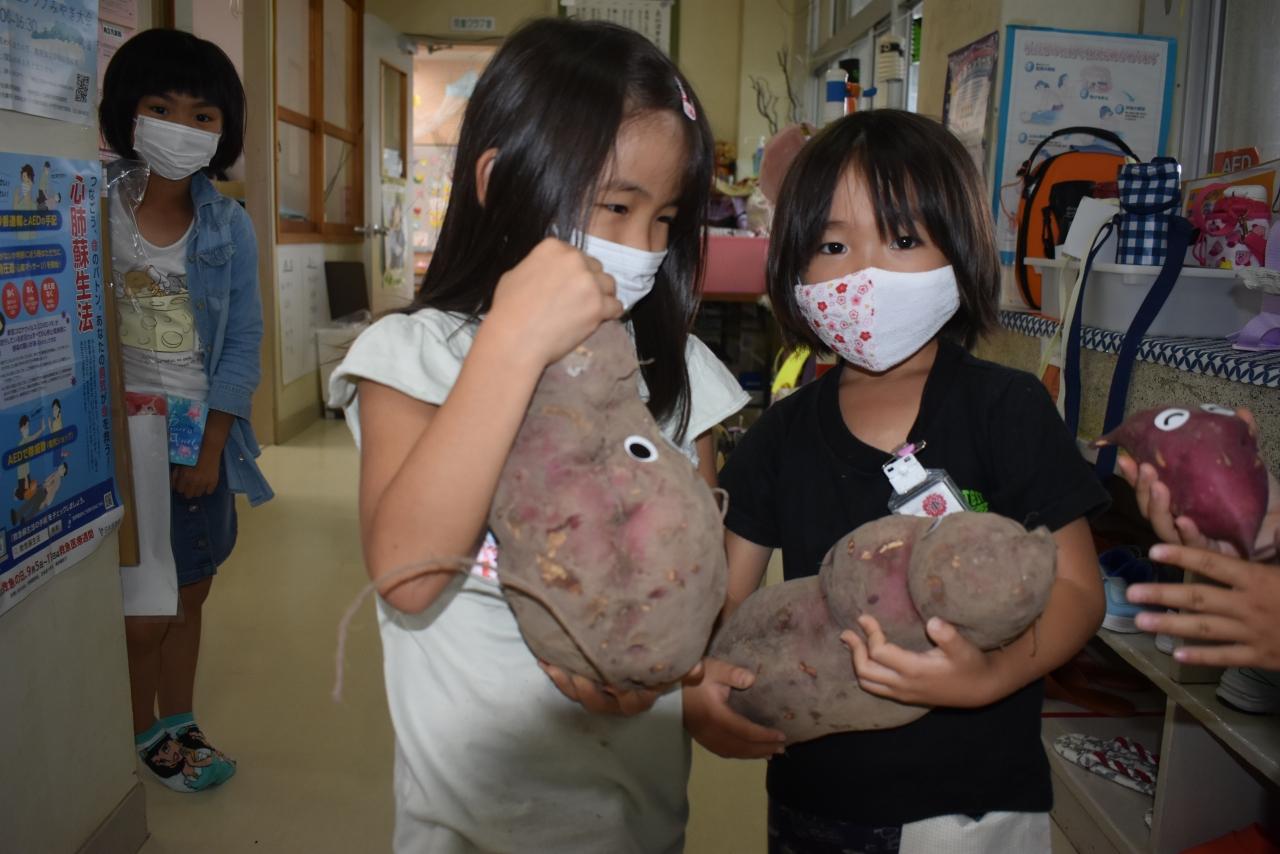 巨大サツマイモを持つ児童